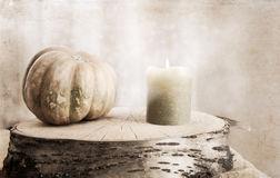 Small pumpkin and burning candle Stock Photos