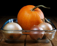 Small pumpkin and onions in a  plate Royalty Free Stock Photography
