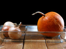 Small pumpkin and onions in a plate Royalty Free Stock Photos