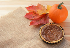 Small pumpkin pie with gourd and autumn leaves Royalty Free Stock Image