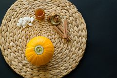 Small pumpkin with seeds, little glass can of honey, walnuts and cinnamon sticks on a circle mat/napkin made of water hyacinth on royalty free stock image