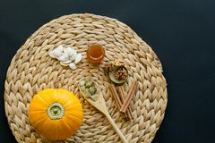 Small pumpkin with seeds, peeled seeds in wooden spoon,  little glass can of honey, walnuts and cinnamon sticks on a circle mat/na royalty free stock image