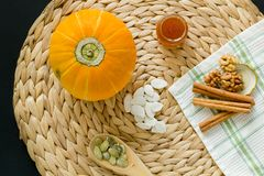 Small pumpkin with seeds, peeled seeds in wooden spoon,  little glass can of honey, walnuts and cinnamon sticks on a circle mat/na stock photography