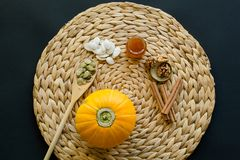 Small pumpkin with seeds, peeled seeds in wooden spoon,  little glass can of honey, walnuts and cinnamon sticks on a circle mat/na stock image