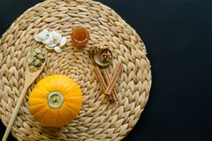 Small pumpkin with seeds, peeled seeds in wooden spoon,  little glass can of honey, walnuts and cinnamon sticks on a circle mat/na stock photo