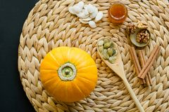 Small pumpkin with seeds, peeled seeds in wooden spoon,  little glass can of honey, walnuts and cinnamon sticks on a circle mat/na stock images