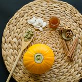 Small pumpkin with seeds, peeled seeds in wooden spoon,  little glass can of honey, walnuts and cinnamon sticks on a circle mat/na royalty free stock photography