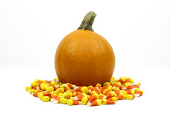 Small pumpkin surrounded by candy corn isolated Stock Photography