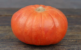 Small pumpkin on a wooden background.Kind mini pumpkin. Royalty Free Stock Image