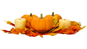 Small pumpkins and candles with fall leaves Royalty Free Stock Image