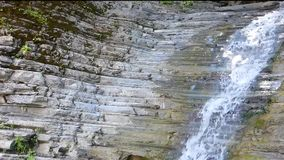 Small pure waterfall on stone wall. Clean water fall from old rocks. Wet stones with horizontal structure, some moss and white foam. Sunny summer day stock footage