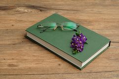 Small purple flowers with a hardcover storybook and spectacles Royalty Free Stock Photos