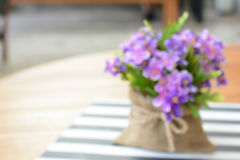 Small purple flowers in jute bag on the table - as blurred background Stock Images