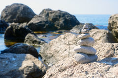 Small pyramid is among the large stones near the Black sea. Royalty Free Stock Photo