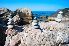 Small pyramids are on the big rocks by the Black sea. Stock Images