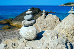 Small pyramids are on the big rocks by the Black sea. Royalty Free Stock Photography