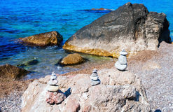 Small pyramids are on the big rocks by the Black sea. Stock Photography