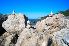 Small pyramids are on the big rocks by the Black sea. Royalty Free Stock Images
