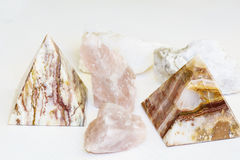 A small pyramids and pink quartz on a white background Stock Photos