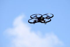 Small quad-motor drone in flight Stock Photos
