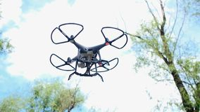 Small quadcopter drone stay in air, four little propellers quickly spin, sky and trees on background. Popular mobile device with e. Mbedded camera for photo and stock video