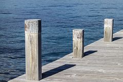 A small quay and its three square mooring poles that create geometric games with the shadows and the symmetry of the wooden planks stock images