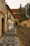 A small quiet street in Prague. A small quiet street and St Castulus Church in background. Prague, Czech Republic Stock Photo