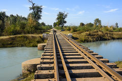 Small rail track bridge over a canal. Small rusty rail track bridge over a canal in rural area Royalty Free Stock Image