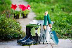 Small rain boots and garden tools Royalty Free Stock Photo