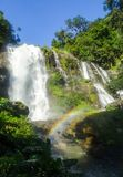 A small rainbow below a waterfall surrounded by green plants stock image