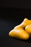 Small raw gourmet potatoeson black background. Small raw gourmet potatoes Stock Photo