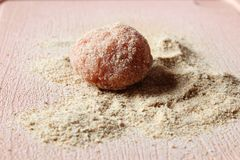Small raw meatball breaded on hill of crackers stock images
