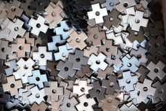 Small raw steel parts. Bulk raw metal parts cross shaped with hole Stock Images