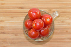 Small raw tomato in glass on wooden background. Tomato in a cup on wood Royalty Free Stock Photography