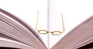 Small reading glasses on open book Royalty Free Stock Photos