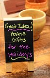 Small chalkboard sign with ideas for hostess gifts. Small rectangular chalkboard sign on shelf, advertising the fact that the shop has great hostess gifts at stock images