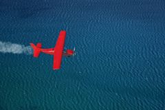 Small red airplane flies over a sea stock images