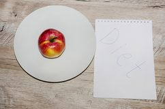 Small, red apple on a white plate and a notepad on a gray, wooden table royalty free stock images