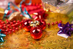 Small red ball near golden gift-box red bead and bow Royalty Free Stock Image