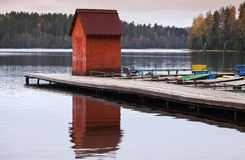 Small red barn on floating pier with moored boats Stock Photo