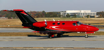 Red private jet. A small red and black private jet on the ground Stock Photography