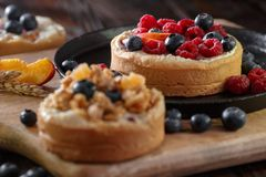 Small red and blue fruit on the cake pie cookie. Filing on a wooden board. Closeup royalty free stock images
