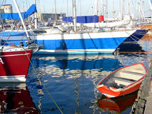 Small red boat. Between big sail boats moored in yacht port stock photography