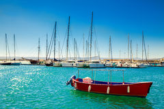 Small red boat in front of the yachts Stock Images