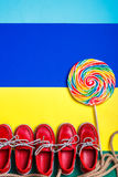 Small red boat shoes, lollipop Royalty Free Stock Photography