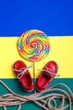 Small red boat shoes, lollipop Stock Photography