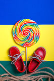 Small red boat shoes, lollipop Royalty Free Stock Photos