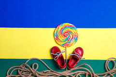 Small red boat shoes, lollipop Stock Photos