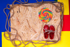 Small red boat shoes, lollipop. Small red boat shoes near big multi-colored lollipop  and rope on wooden desk with colored background.  Top view, Frame. copy Stock Photos