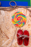 Small red boat shoes near big multi-colored lollipop  and rope on wooden desk with colored background.  Top view, Frame. Small red boat shoes near big multi Stock Images